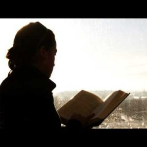 Silhouette of a person reading a book.