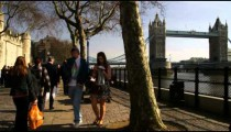 Tower Bridge with people walking by in the foreground in London England.