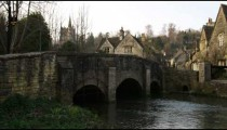 Royalty Free Stock Footage of Pan of an old stone village bridge and a stream.