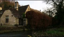 Royalty Free Stock Footage of Old stone houses panning to a stream in England.