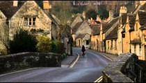Royalty Free Stock Footage of Biker passing through an old stone village in England.