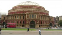 People and cars passing Royal Albert Hall in London.