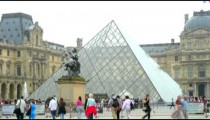 People passing by the glass pyramid of the Louvre Museum.