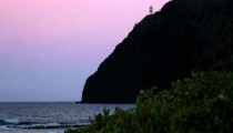Lighthouse on a rocky cliff above the ocean at sunset in Hawaii.