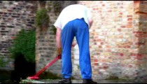 Man next to a canal sweeping a patio.