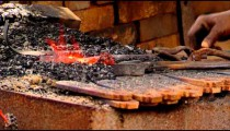 Royalty Free Stock Footage of Blacksmith stirring coals of a fire.
