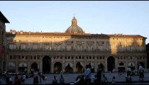 Royalty Free Stock Footage of People passing by a plaza at sunset in Bologna Italy.