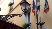 Royalty Free Stock Footage of Street light and flags by a building in Bologna Italy.