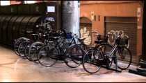 Old bikes parked at a rack in a mall in Bologna Italy.