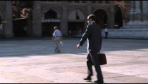Follow pan of business man walking through a plaza in Bologna Italy.