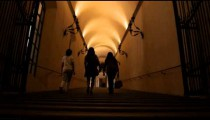 People walking up a dark staircase in Bologna Italy.