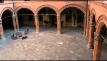 Pan from windows to a courtyard with arches in Bologna Italy.