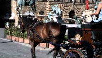 Horse and carriage passing a statue in Italy.