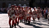Clip of men in fancy attire playing instruments in a parade in Italy.