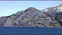 Traveling time-lapse of a rocky outcropping alongside the water in Glacier Bay, Alaska.