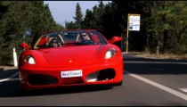 Two Ferraris driving on a road in Italy.