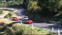 Two Ferraris driving on a winding country road in Italy.