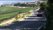 Two Ferraris driving down a country road in Italy.