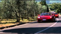 Shot of two Ferraris driving by on a country road in Italy.