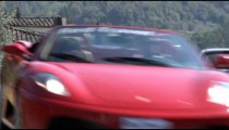 Shot of two Ferraris driving by on a road in Italy.