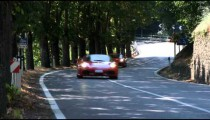 Clip of two Ferraris driving by on a country road in Italy.