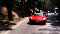 Shot of two Ferraris driving down an Italian country road.