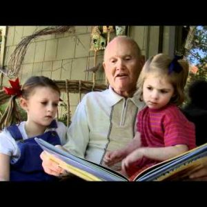 Grandpa reading a book to his granddaughters outside.