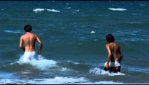 Two boys playing in the ocean at Punta Ala Italy.