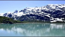 Traveling view of snow covered mountains and small ice glaciers floating in Glacier Bay