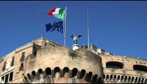 Two flags on a flag pole atop a stone structure in Rome Italy.