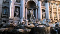 Tilt down from ancient Roman building to small fountain in Rome.
