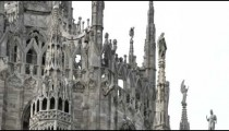 Stone architecture and a gold statue in Milan Italy.