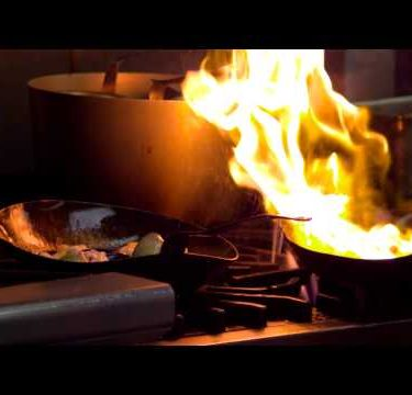 Close-up of a chef cooking over an open flame in Salt Lake City.