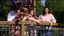 Slow motion shot of a family in a beautiful garden on a bridge.