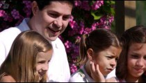 Close-up slow motion shot of a family on a bridge in a beautiful garden.