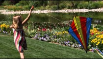 Slow motion shot of a girl playing with a kite in beautiful gardens.