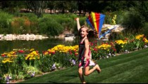 Slow motion shot of a girl flying a kite in beautiful gardens.