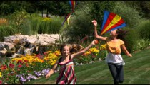 Slow motion of two sisters playing with kites in beautiful gardens.