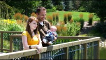 Clip of a young family on a deck overlooking a pond.