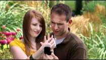 Young man proposes to a young woman in a beautiful garden.