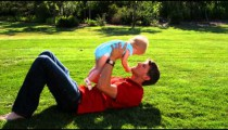 Slow motion shot of a young couple with their baby girl playing in a garden.