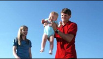Slow motion shot of a couple with their baby girl playing in a garden.