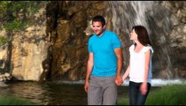 Couple walking through a garden in front of a waterfall.