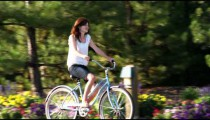 Young woman riding a bike through a beautiful garden.