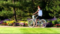 Shot of a young woman riding a bike through a beautiful garden.