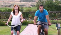 Slow motion shot of a young couple riding bikes through a beautiful garden.