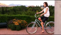 Clip of a young woman riding a bike in a garden.