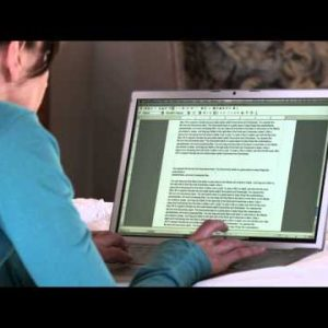 Woman typing and printing on a laptop in pajamas.