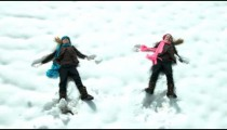 Twin girls fall back into a snow drift.