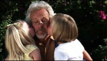 Clip of granddaughters kissing their grandfather.